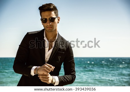 Handsome man in classical suit on beach - stock photo