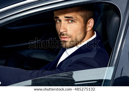 handsome man in costume inside the car
