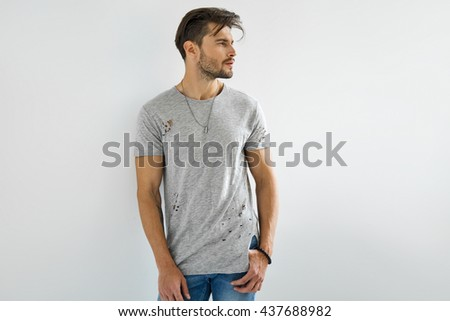 Handsome man in grey t-shirt posing on white background - stock photo