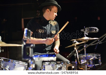 Handsome man in hat and black shirt plays drum set in night club. - stock photo