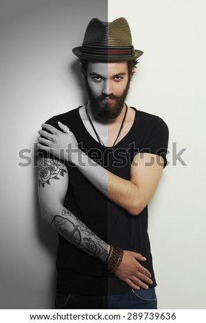 handsome man in hat.Brutal bearded boy with tattoo.monochrome half