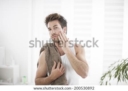 handsome man in his bathroom towel on shoulders - stock photo