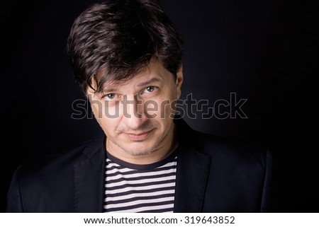 Handsome man in his 40's looking in the camera with clear, candid eyes. Wearing T-shirt with stripes and a black jacket. - stock photo