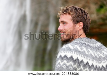 Handsome man in Icelandic sweater outdoor smiling by waterfall on Iceland. Portrait of good looking male model looking to side in nature. - stock photo