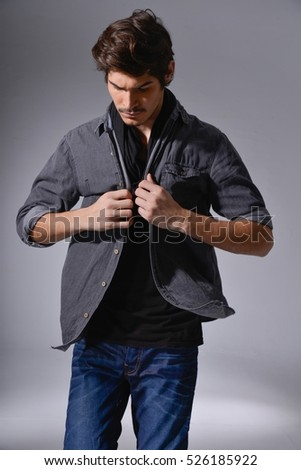 handsome man in jeans and leather jacket-gray background