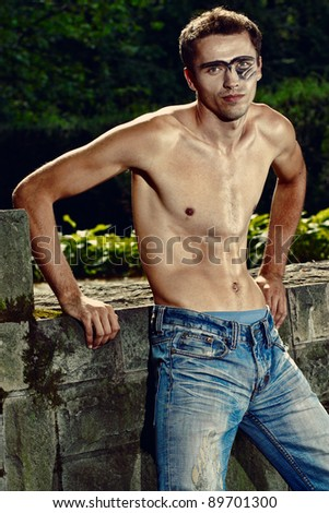 handsome man in jeans trousers, male model with makeup on his face - stock photo