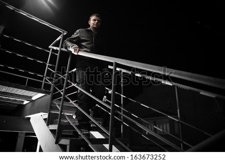 Handsome man in leather coat going down staircase at night - stock photo