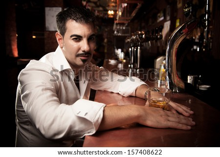 Handsome man in shirt sitting near bar desk with whiskey glass