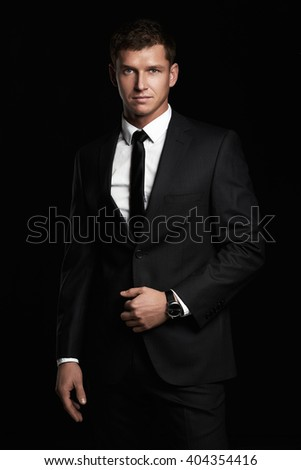 handsome Man in suit and tie. Businessman standing on black background