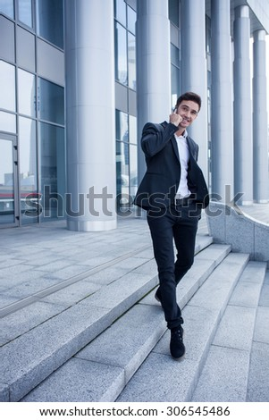 Handsome man in suit is going down steps from his office. He is using a telephone for communication with his business partner. The man is smiling. Copy space in left side - stock photo