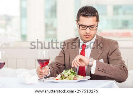 Handsome man in suit is sitting at the table and looking at his watch attentively. He is waiting for his business partner. The man is drinking wine and eating a salad. Copy space in left side - stock photo