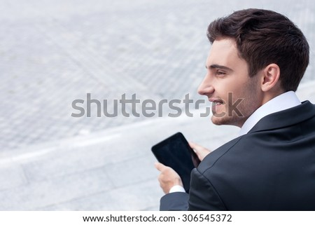 Handsome man in suit is sitting on steps and holding a laptop. He is looking aside and smiling. The man is waiting for his colleague. Copy space in left side - stock photo