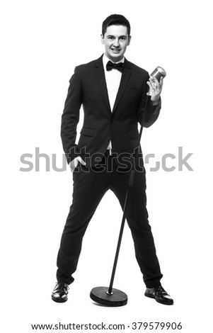 Handsome man in suit singing over the retro microphone. Isolated on white background. Singer concept. Monochrome photography. - stock photo