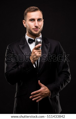 Handsome Man in suit singing with the microphone and smile. Isolated on black background. Showman concept.