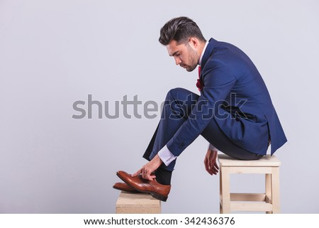 handsome man in suit sitting on chair in studio cleaning his brogue shoes - stock photo