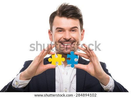 Handsome man in suit trying to connect puzzle pieces. White background. - stock photo