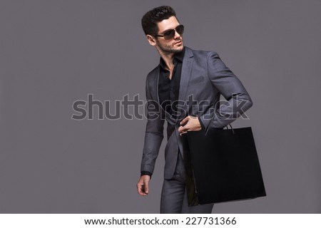 Handsome man in suit with shopping bag - stock photo