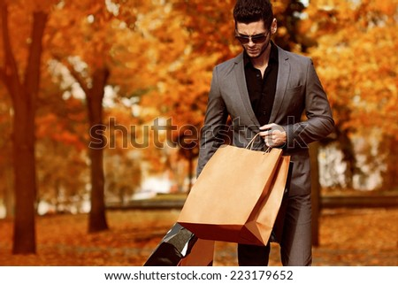 Handsome man in suit with shopping bags. Autumn. - stock photo