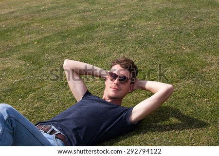 Handsome man in sunglasses relaxing on green grass  - stock photo