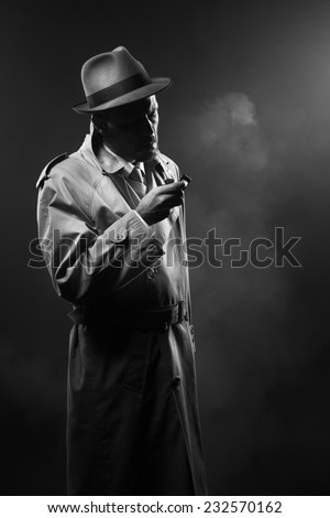 Handsome man in trench coat lighting a cigarette in the dark - stock photo