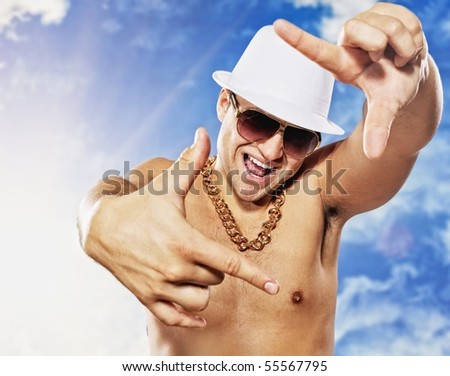 Handsome man in white had in front of blue sky - stock photo