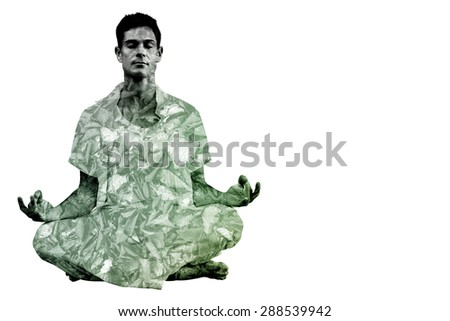 Handsome man in white meditating in lotus pose against detail shot of dry leaves - stock photo