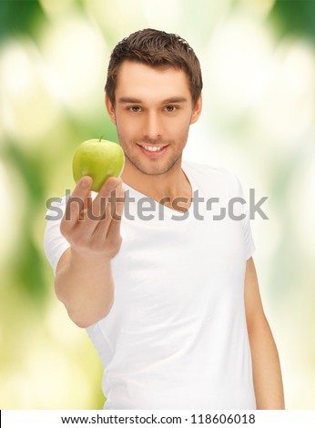 handsome man in white shirt with green apple
