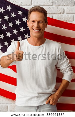 Handsome man in white sweatshirt is showing Ok sign, looking at camera and smiling while standing against American flag