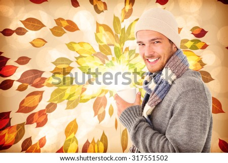 Handsome man in winter fashion holding mug against autumnal leaf pattern in warm tones - stock photo
