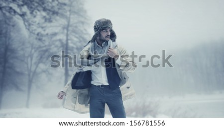 Handsome man in winter scenery - stock photo