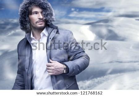 Handsome man in winter snow - stock photo
