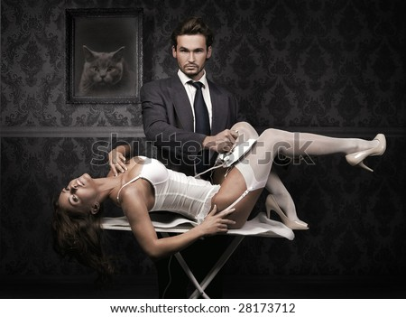 Handsome man ironing attractive brunette - stock photo