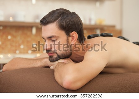 Handsome man is getting stone massage at spa. He is lying with relaxation. The man closed his eyes with pleasure - stock photo