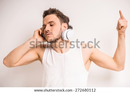 Handsome man is listening to music with headphone over gray background. - stock photo