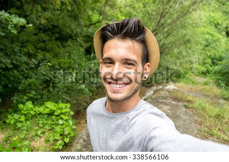 Handsome man is taking a selfie outdoor - caucasian people - nature, people, lifestyle and technology concept - stock photo