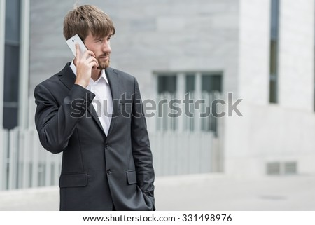Handsome man is talking on mobile phone - stock photo