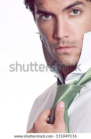 Handsome man is wearing is stylish green tie . Studio shot - stock photo