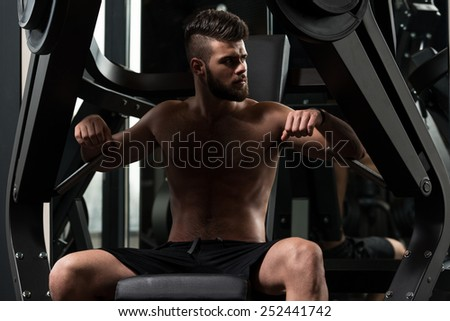Handsome Man Is Working Out Chest On Machine In A Modern Gym - stock photo