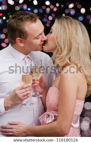 Handsome man kissing girlfriend  at party - stock photo