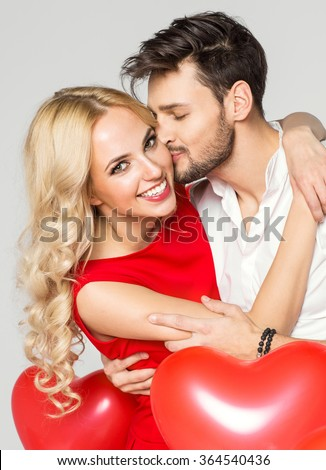 Handsome man kissing his girlfriend cheek. Valentine's day - stock photo