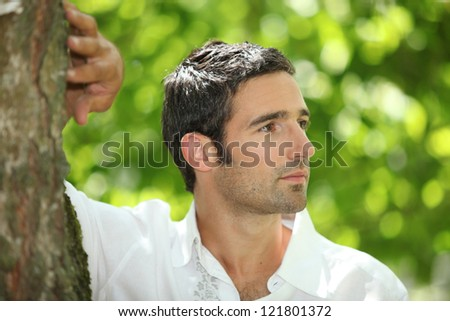 Handsome man leaning against a tree in a park - stock photo