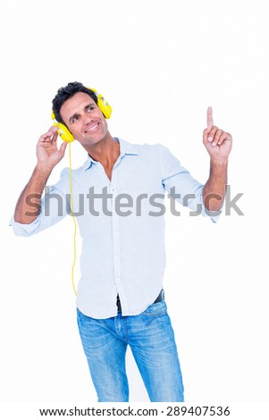 Handsome man listening music with headphone on white background - stock photo