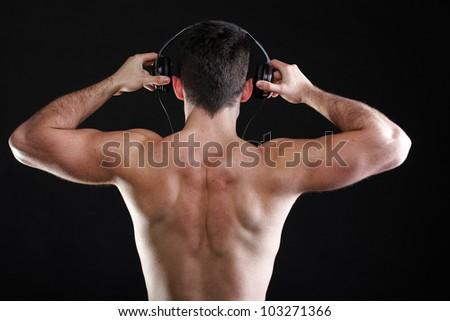 handsome man listening to music on headphone black background - stock photo