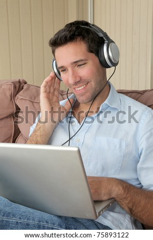 Handsome man listening to music on internet - stock photo