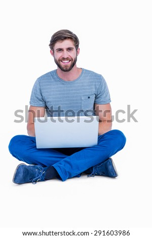 Handsome man looking at camera and using laptop on white background - stock photo