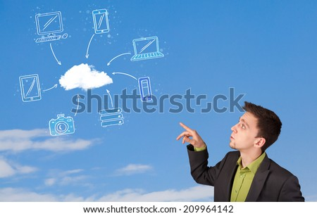 Handsome man looking at cloud computing concept on blue sky - stock photo