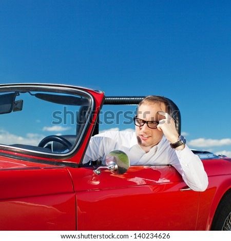 Handsome man looking out on his convertible car - stock photo