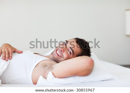 Handsome man lying in his bed smiling - stock photo