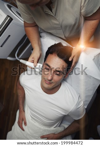 Handsome man lying on the medical chair having facial laser rejuvenation procedure at the professional aesthetic clinic, satisfied customer in white t-shirt - stock photo