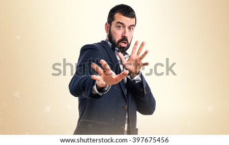 Handsome man making stop sign over ocher background
